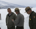 Two man wearing campaign hats talk with Secretary Zinke, snow and mountains in background