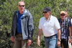 Secretary Zinke and three others along a trail next to pine
