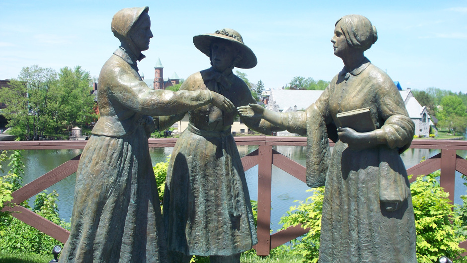 Statues of 3 women against a blue sky; women in hat in a pose introducing woman with no hat carrying book, to a woman in a bonnet
