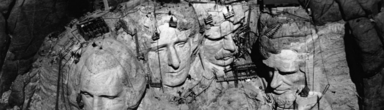 Mount Rushmore under construction. RIgging visible. Black and white photo.