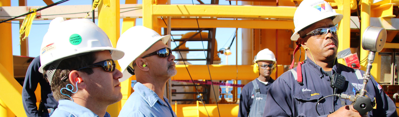 BSEE inspectors monitor a worker at a pressure gauge.