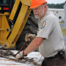 Fish and Wildlife Service Employee tightens equipment to a flatbed.