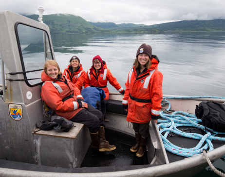 A group of female U.S. Fish and Wildlife Service employees heading out in a Service boat to conduct field biology research.