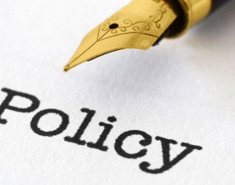 The word policy typed on paper and an ink pen.