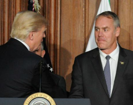 President Trump and Secretary Zinke shake hands at a lectern.