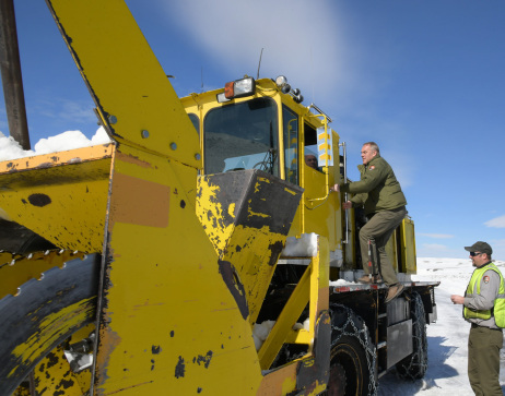 Secretary Zinke climbs into yellow snow removal vehicle on a clear day