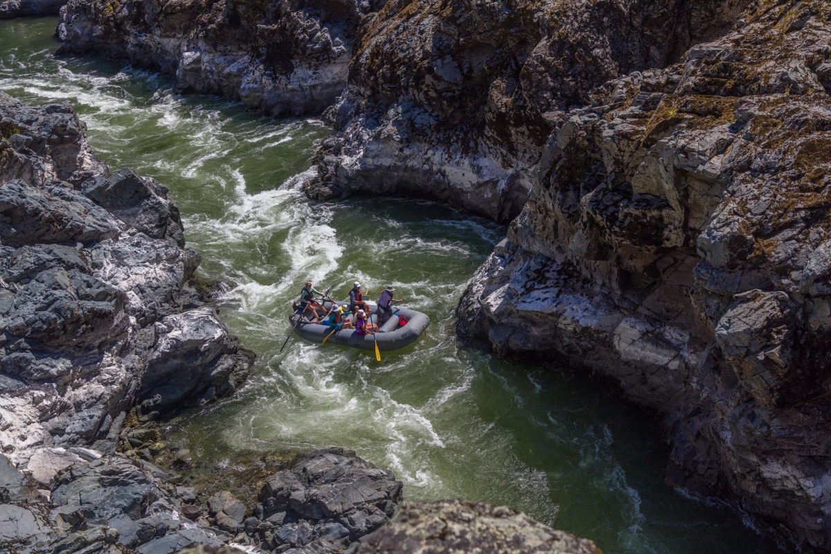 A family rafts down the Rogue River, encompassed by large rock walls.
