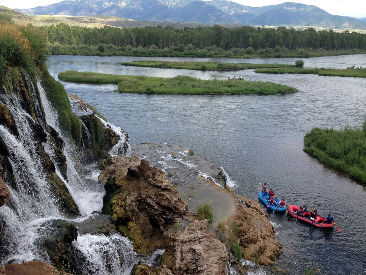 Two rafts float down the river as water flows over a small falls with mountains in the background.