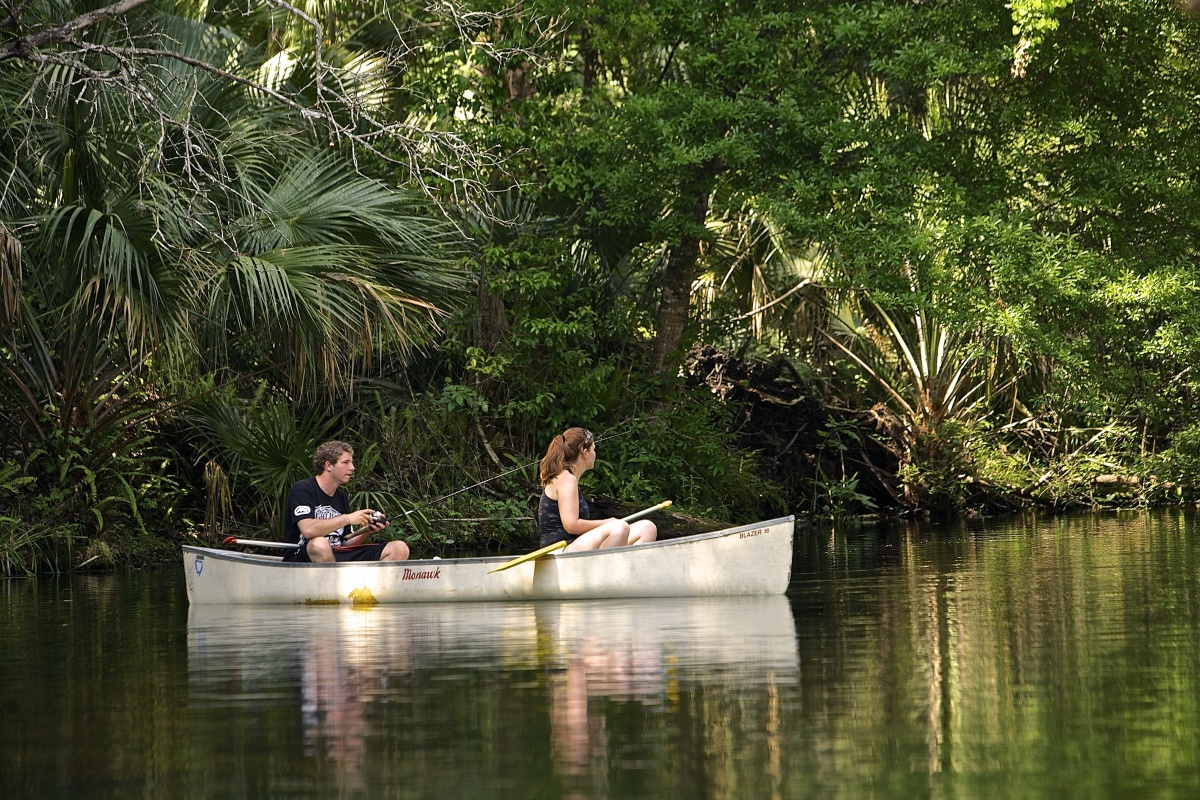 A man and a woman sit in a canoe along the bank of the Wekiva River. The man fishes while the woman watches.