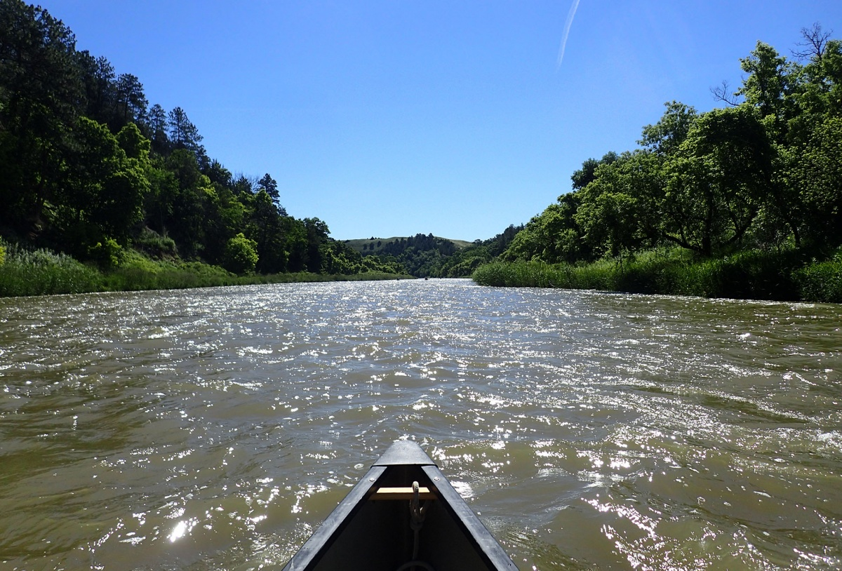 The front of a canoe sits at the bottom of the picture, showing a wide view of slow waves on the Niobrara River.