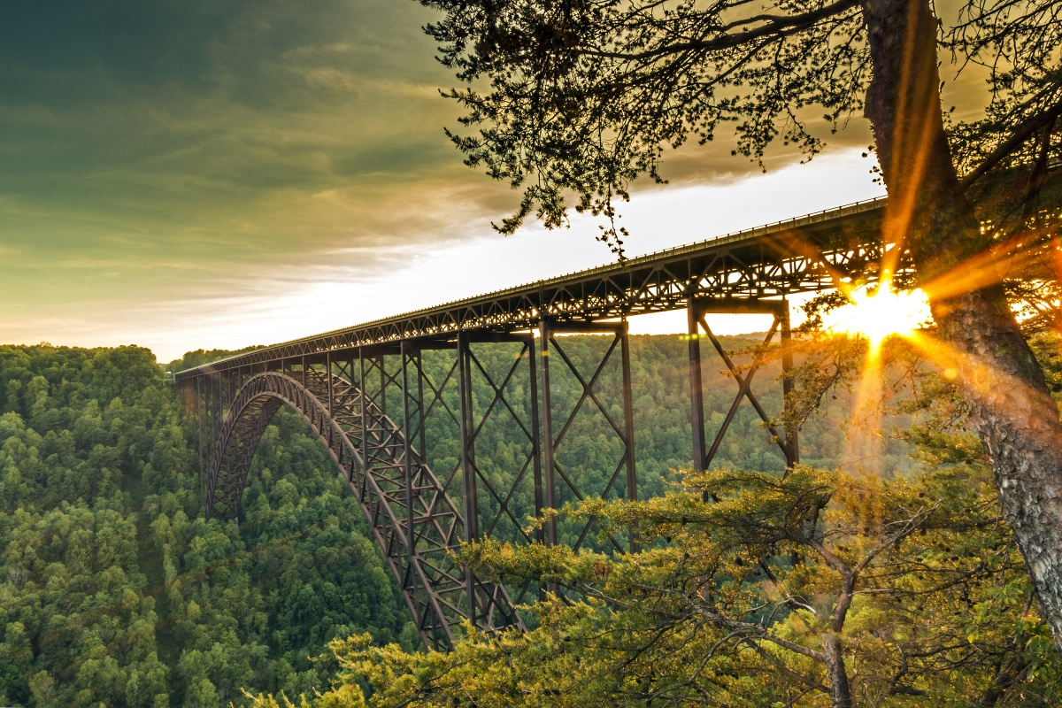 The new river gorge bridge shines brightly as the sun reflects of it.
