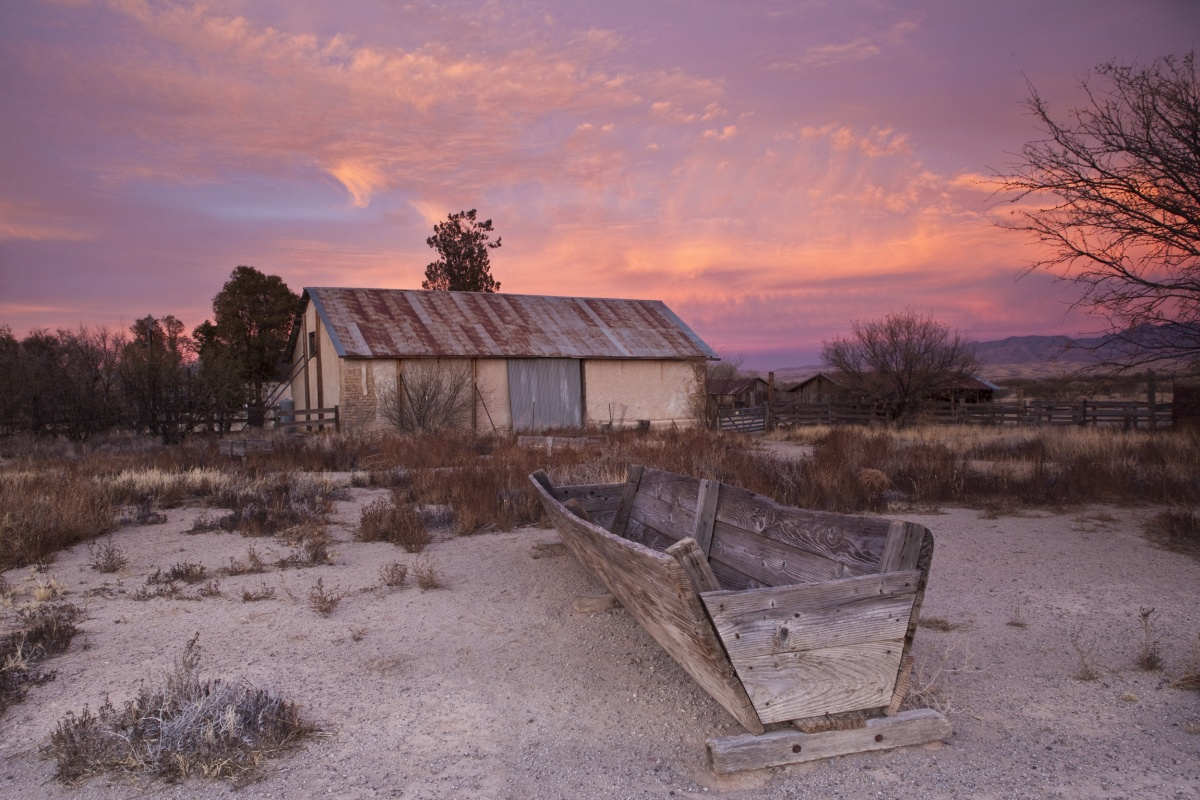 A small ranch house stands among dry, brown and grey field with a warm pink and purple sky behind it.