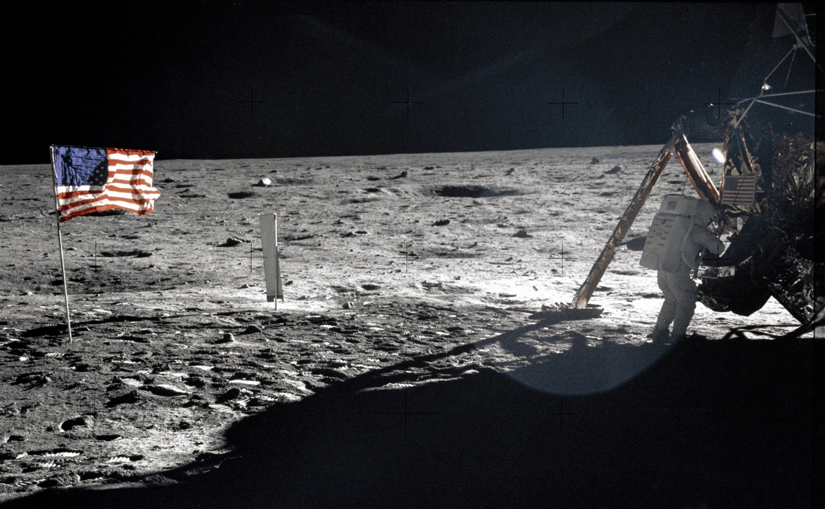 This photo appears black and white, as the lunar surface contrasts against the dark sky. However, on the right side of the photograph, an astronaut climbs into a space ship and on the left side, a bright red, white, and blue American flag flies.