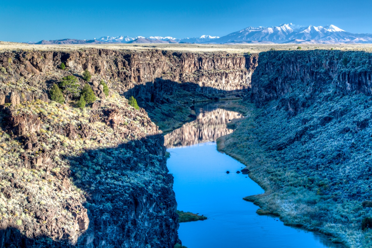 A shadow from the canyon walls falls over the still turquoise blue Rio Grande.