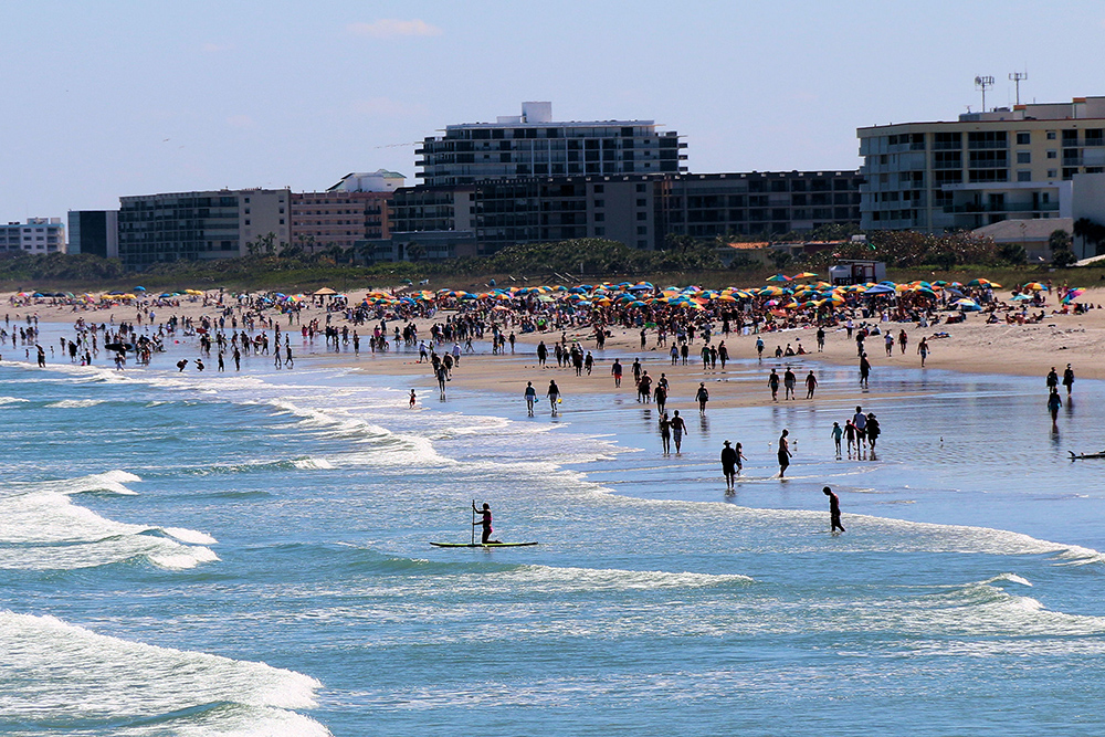 A beach is filled with people in the water and on the sand. Large buildings line the far side of the beach.