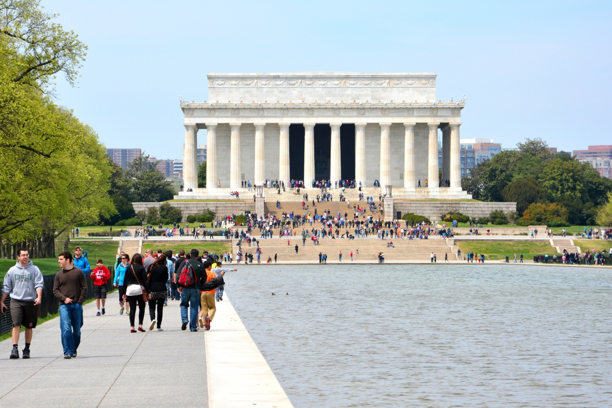A large white monument stands behind a reflection pool and is surrounded with bright green trees and tons of people walking alongside the pool and monument.