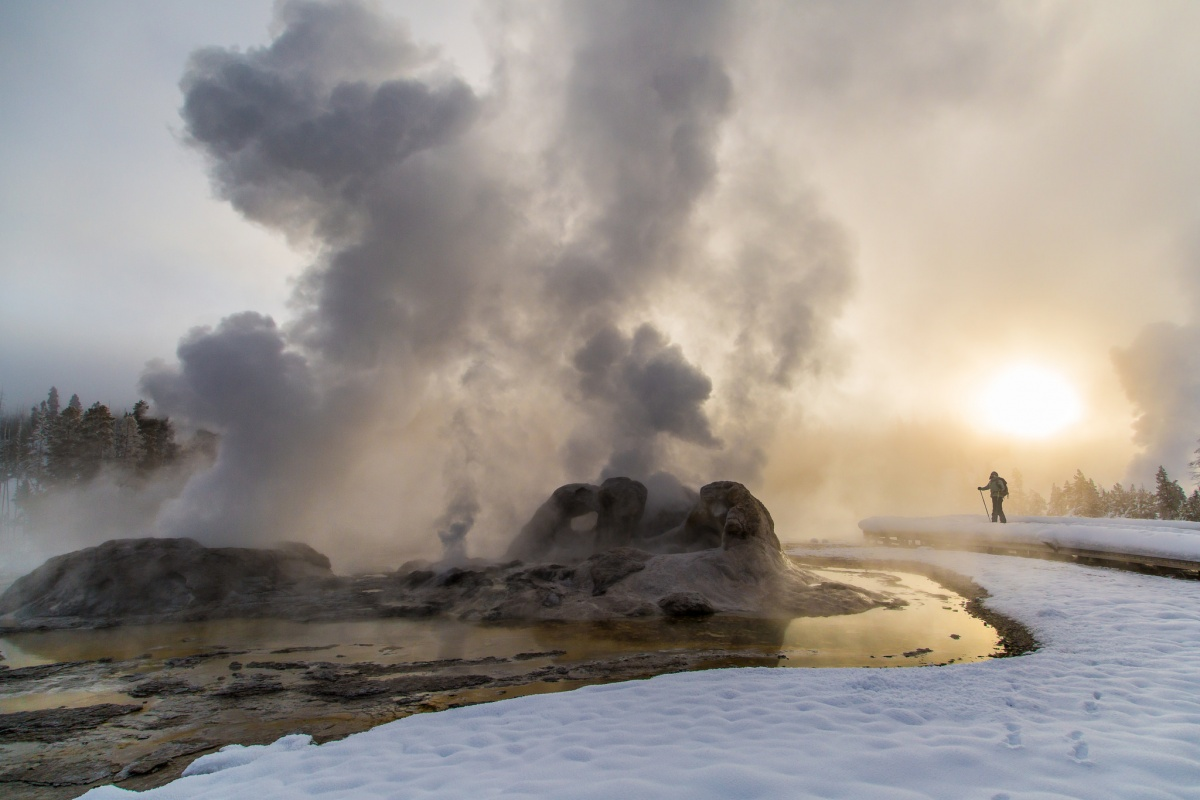 steam erupting from geyser at sunrise