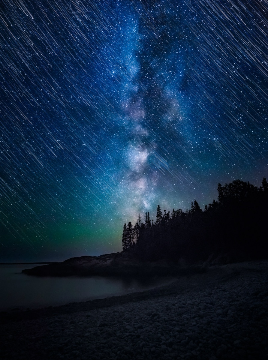 Shooting stars fill the bright blue sky, looking almost like rain. The Milky Way stands in the center of the photo and illuminates dark trees and the shoreline.