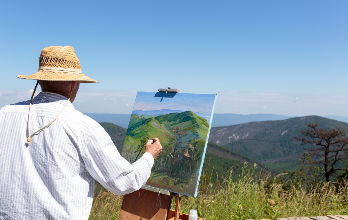 A man with a canvas on an easel stands on a mountaintop using a paint brush to paint the mountain landscape.
