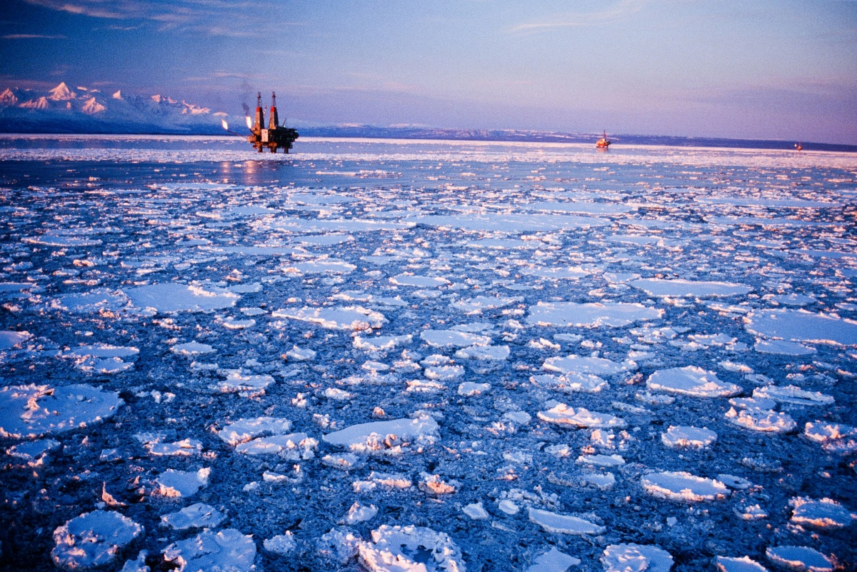 An drilling platform stands above the still water of an ice covered ocean.
