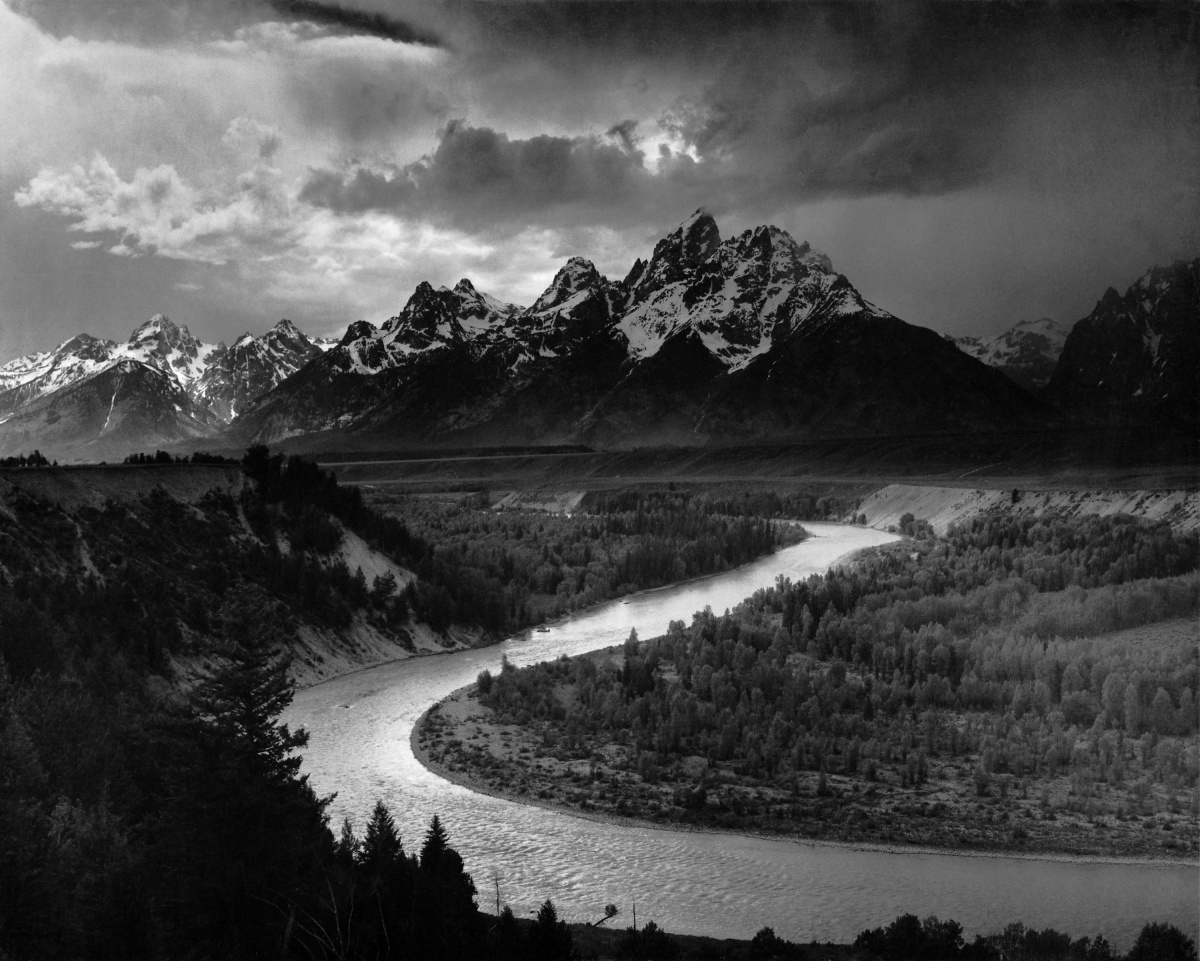 A black and white photo shows a river curving around trees with tall jagged mountains rising in the background.