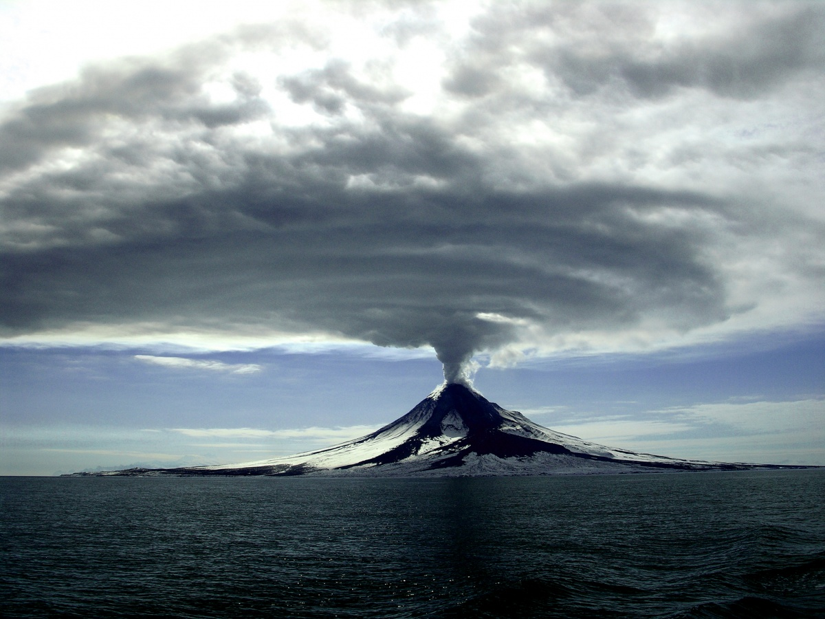 A huge cloud of smoke expands across the sky as it erupts from a cone shaped volcano on the shore of the ocean.