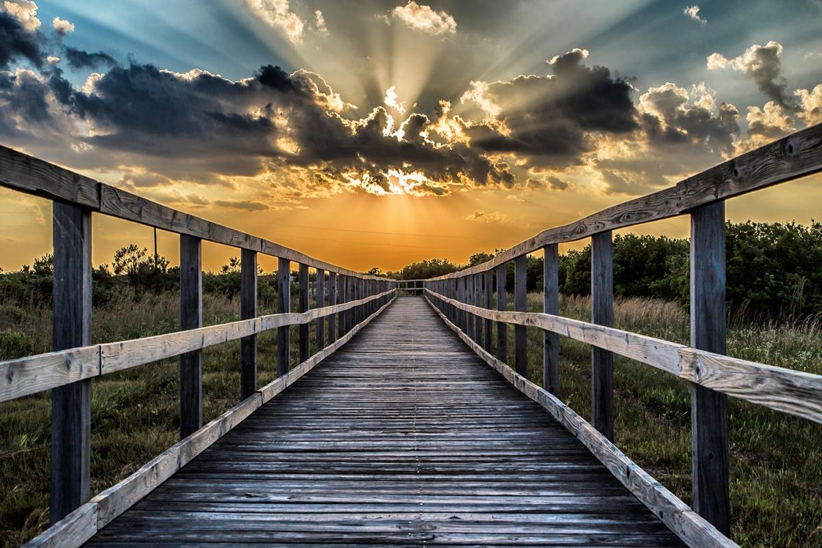 sunlight bursting through clouds over a walkway