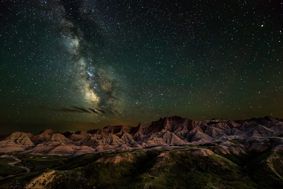 The Milky Way appears in a green starry sky, illuminating the mountain-filled landscape below.