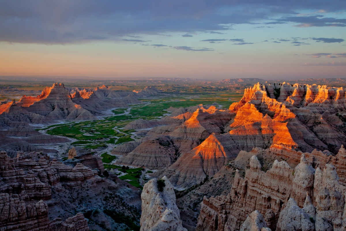 The sun sets over the jagged rock formations of the badlands.