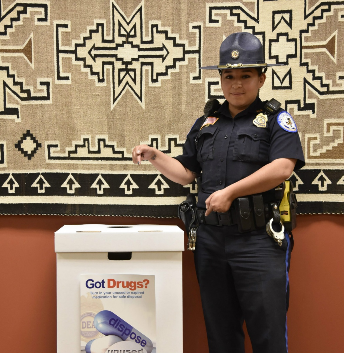 A female police officer in a navy blue uniform and wide hat stands inside next to a box for turning in unused medicine.