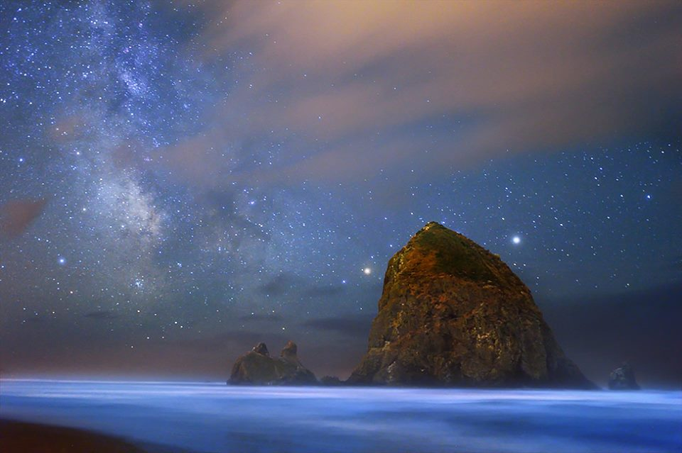 A bioluminescence effect encircles an island of the Oregon Coast, illuminating the water.