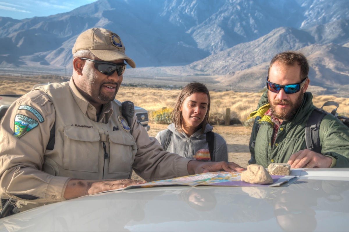 An African American man in a tan BLM police uniform stands with a white man and woman as they look at a map spread out on the hood of a car with mountains in the background.