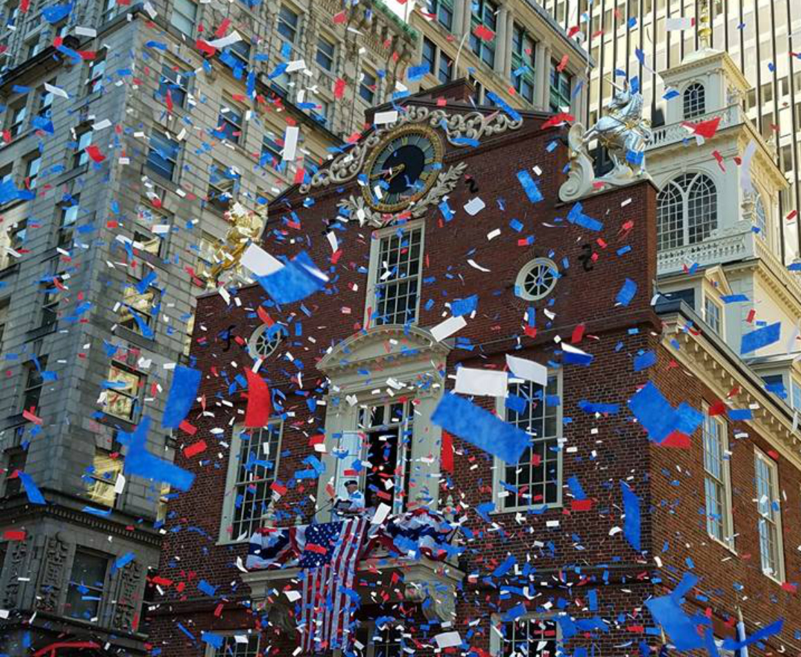 Red, blue and white confetti fall around the Boston National Historic Park.