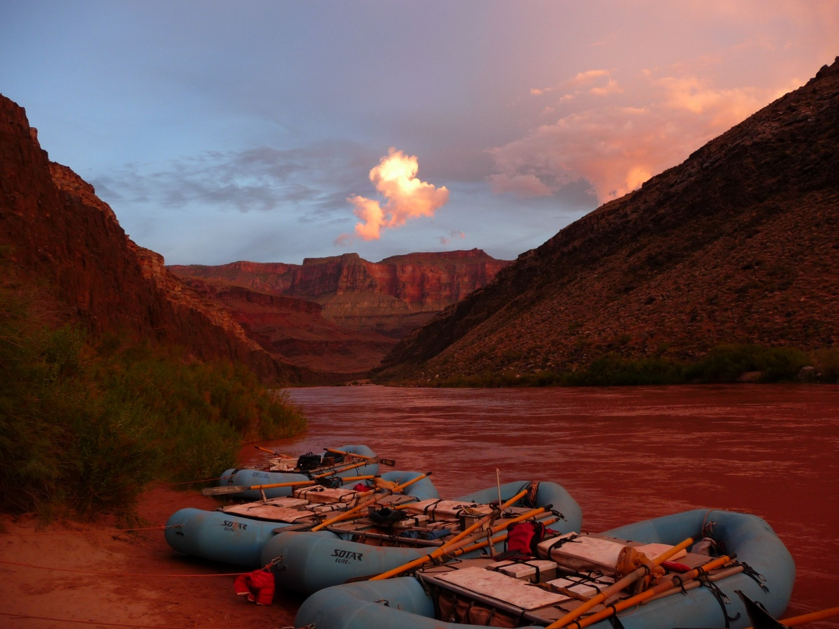 Three rafts rest along the red banks of the river with the canyon walls jutting up on either side.