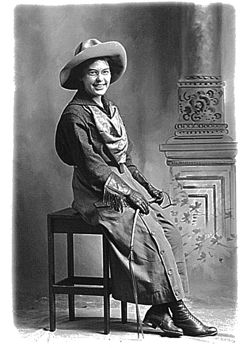 A historic back and white photo of a woman wearing a cowboy hat and a riding dress sitting on a small table.