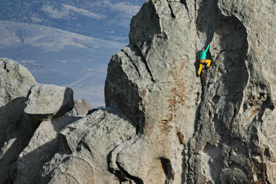 A lone climber scales the grey granite face of the rock called Anteater.