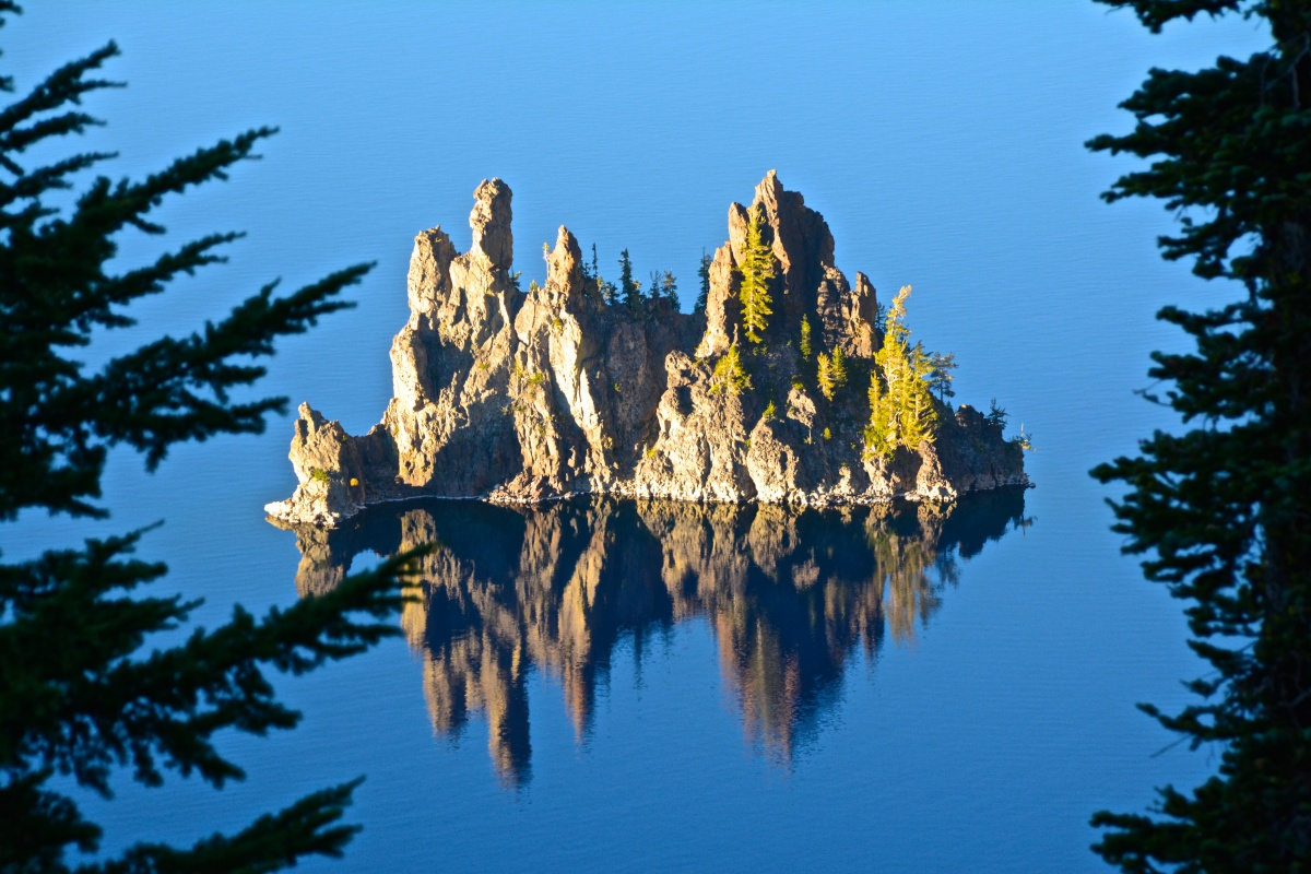 A small island with tall rock towers and a few trees rises out of the still waters of a lake.
