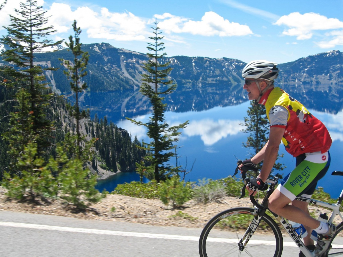 A thin, older white man wearing a helmet and bright biking clothes rides a bicycle on a road past a blue mountain lake.