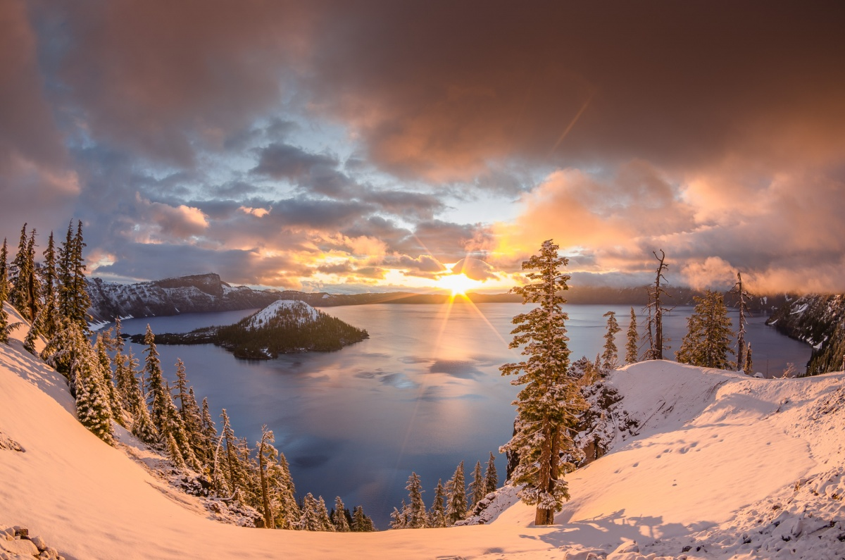 The sunrise peaks over the lip of a snow covered ridge that surrounds a circular mountain lake.