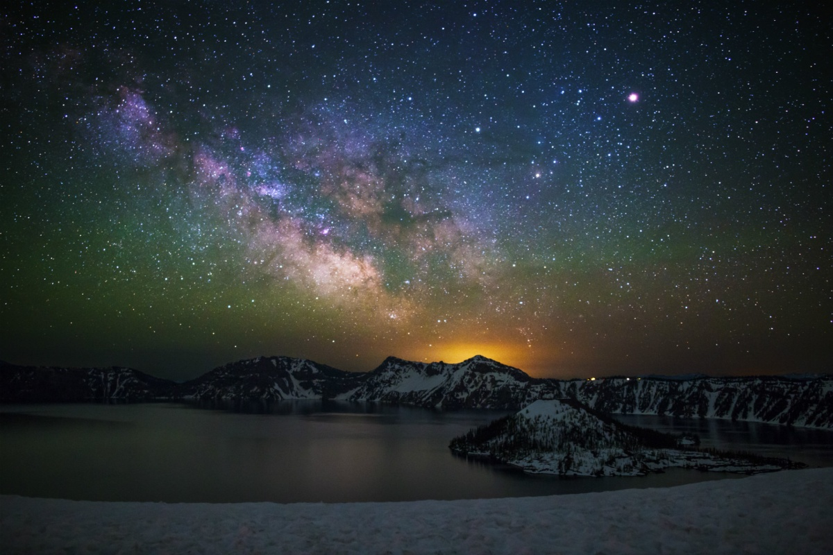 A dazzling night sky of stars and the milky way shines over snow covered cliffs sloping down to a wide circular lake.