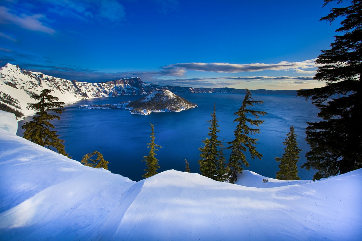 Crater Lake is a large, circular blue lake surrounded by a high rim of snow covered cliffs and a large pyramid shaped islands rises out of its calm waters.