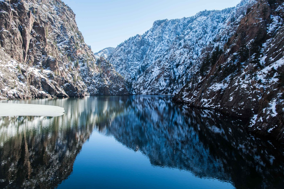 Snow covered walls of a canyon slope down to the flat, blue waters of a lake.