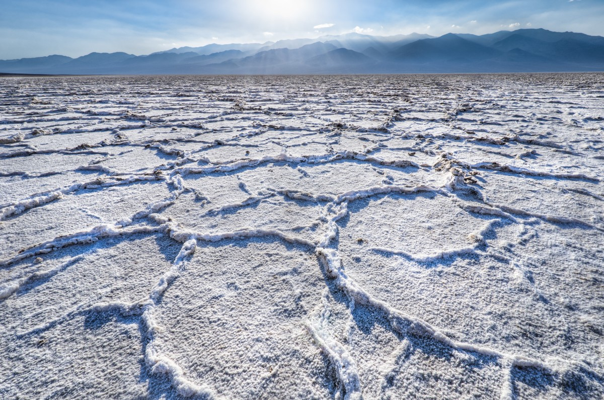 A flat desert plain showing ripples of white salt runs to a low range of mountains under a sunny blue sky.