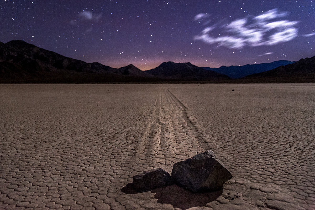 Two rocks sit at the end of long drag marks on a flat desert plain under a starry night sky.