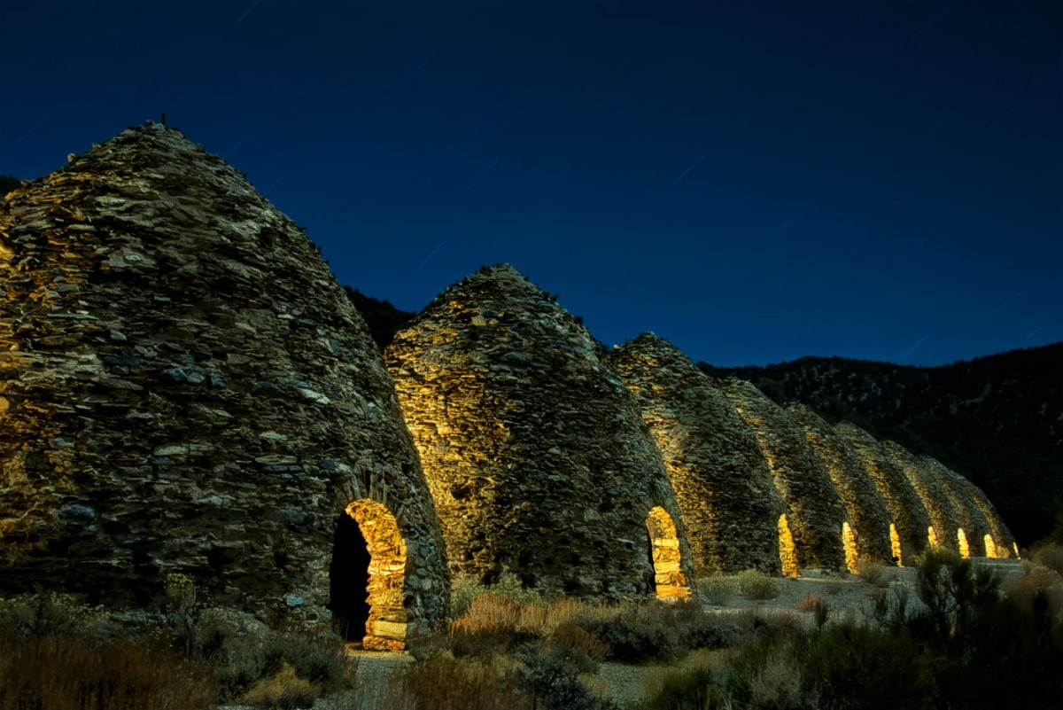 Nine rough stone cone shaped buildings with low arched doors stand in a line on a grassy plain under a night sky.