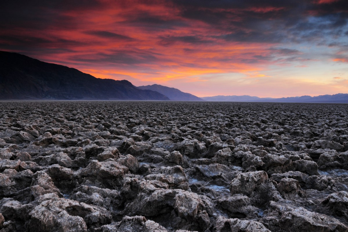 A flat desert plain bordered by mountains is covered in low jagged rocks under a pink sky.