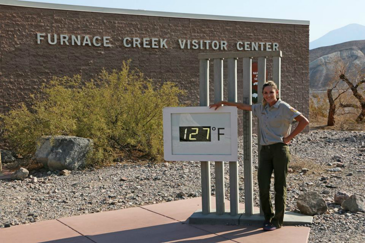 A young woman stands next to an outdoor digital thermometer that shows 127 degrees.