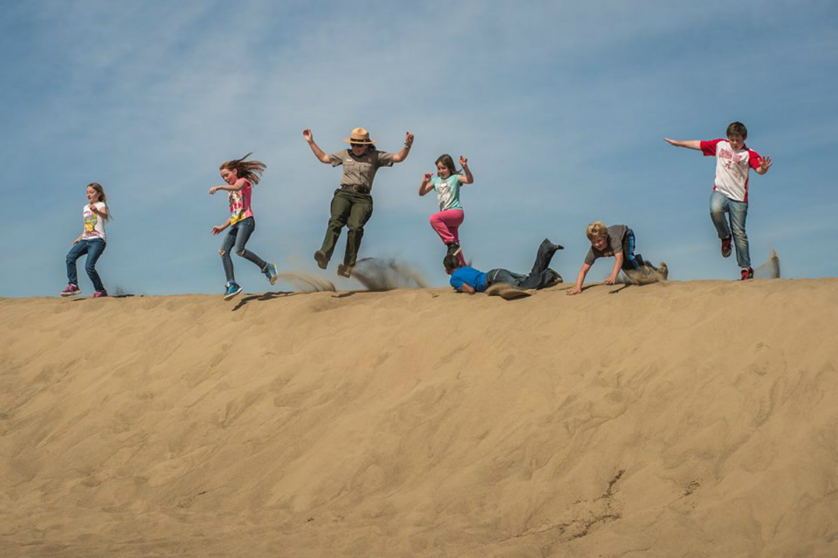 A female park ranger runs down a large sand dune with a group of kids.