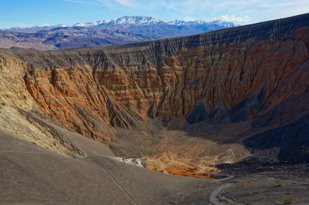A view looking down into a massive round crater with brown and orange walls sloping down to a sandy bottom.