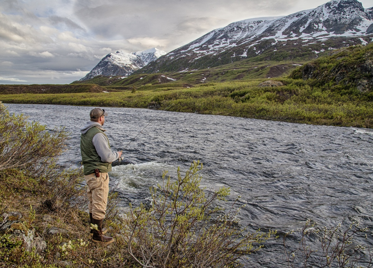 A man holds a fishing rod on a riverbank with a snow capped mountain in the background.